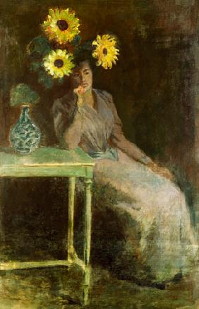 Sedentary woman next to a vase with sunflowers