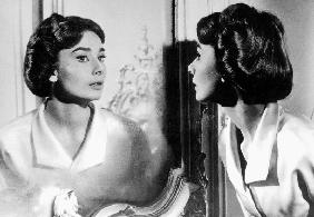 Actress Audrey Hepburn looking at her reflection in the mirror
