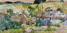 Thatched houses in front of a hill